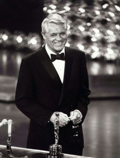 "oldhollywood:  Cary Grant receiving an Academy Honorary Award in 1970 (online here) ""Years ago, when Cary Grant and Dyan Cannon were getting divorced, a perhaps apocryphal story appeared in the scandal sheets: As an example of Grant's supposed irrationality, Cannon cited to the judge Cary's yearly habit of sitting in front of his television and sardonically abusing all the participants. This item, true or not, must have amused nearly everyone in Hollywood, since nearly everyone in Hollywood does pretty much the same thing.  The funny thing is that from all accounts, when the Academy Awards began in 1939, they were conducted in a similar spirit of irreverence, something that has practically disappeared from the event itself. ""They used to have it down at the old Coconut Grove,"" Jimmy Stewart told me in the late 70s. ""You'd have dinner and alawta drinks - the whole thing was…it was just…it was a party. Nobody took it all that seriously. I mean, it was swell if ya won because your friends were givin' it to you, but it didn't mean anything at the bawx office or anything. It was just alawta friends gettin' together and tellin' some jokes and gettin' loaded and givin' out some little prizes. My gawsh, it was..there was no pressure or anything like that."" Cary Grant corroborated this to me: ""It was a private affair, you see - no television, no radio, even - just a group of friends giving each other a party. Because, you know, there is something a little embarrassing about all these wealthy people publicly congratulating each other. When it began, we kidded ourselves: 'All right, Freddie March,' we'd say, 'we know you're making a million dollars - now come up and get your little medal for it!'"" -excerpted from Peter Bogdanovich's Who the Hell's In It"