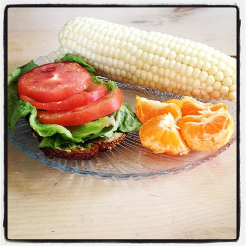 Lunch today. Romaine, avocado, and tomato on whole grain toast with sweet corn and a mandarin orange. So good. :)