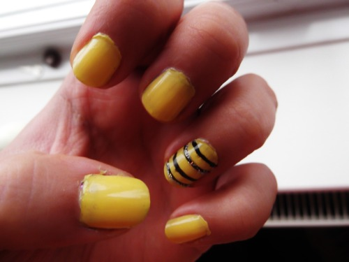 Yellow nails. Ring finger black lines and glitter.