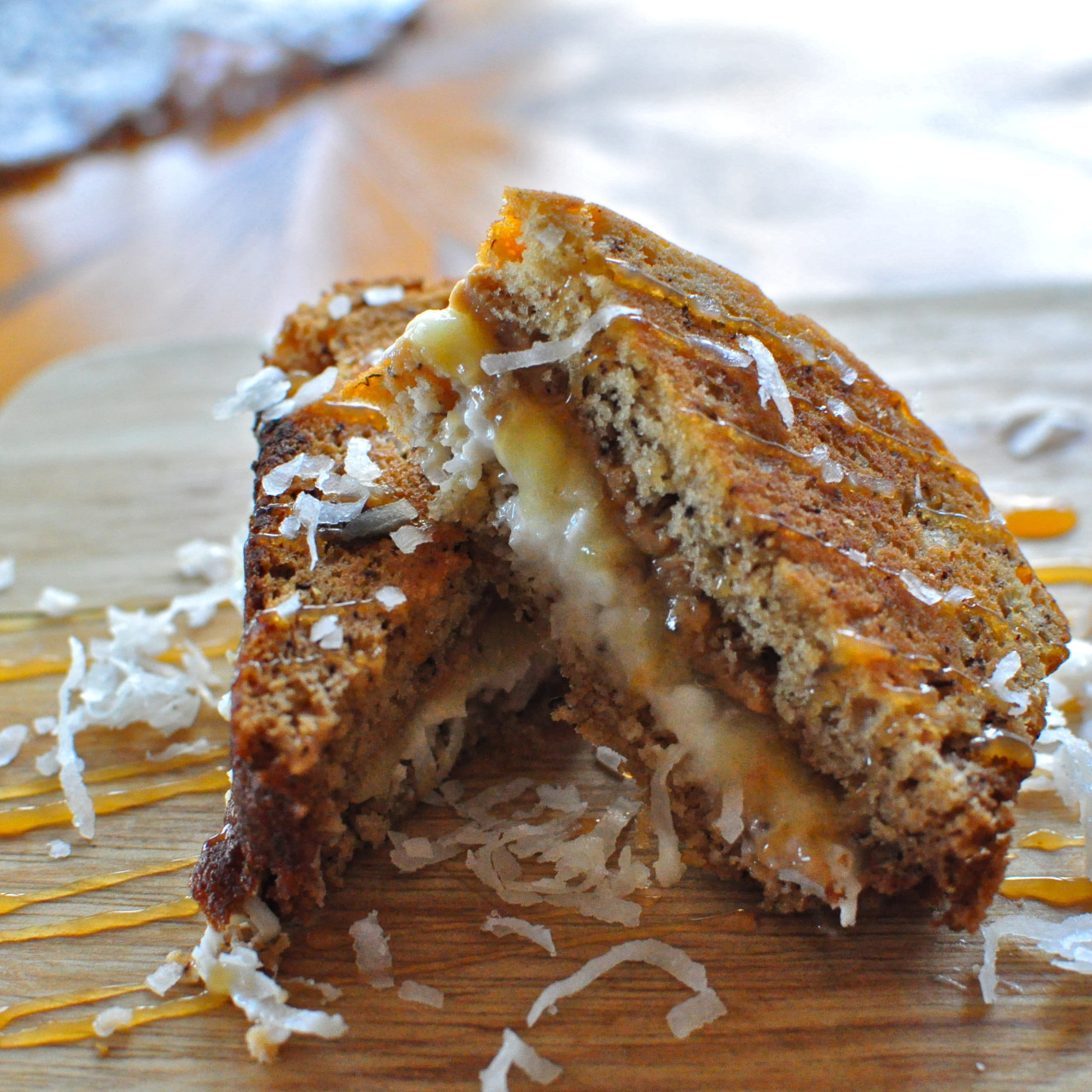 Banana Bread Paninis with Coconut, Peanut Butter, and Bananas [[MORE]] — Bananas and peanut butter is a classic combination, so why not enjoy it as a sandwich?   Add in coconut, caramel, and more bananas, and you will love all the different textures and layers of flavors of this sandwich. Each bite is filled with the crunch from the coconut, creamy peanut butter, and rich, sweet caramel sauce. This sandwich makes for the perfect afternoon treat.   Banana Bread Paninis with Coconut, Peanut Butter, and Bananas 1 tbsp plain greek yogurt 1/4 tsp almond extract 1 tbsp shredded coconut 1 tsp sugar 4 slices banana bread, about 1 inch thick 1/2 banana 1 tbsp peanut butter 2 tsp caramel sauce 2 tsp butter — In a bowl, combine the yogurt, almond extract, coconut, and sugar. Spread the coconut mixture on 2 slices of bread. Slice 1/4 of a banana on top of the coconut.  Spread 1/2 tbsp peanut butter on each of the other two slices of bread. Spread 1 tsp caramel sauce on top of the peanut butter. Take on peanut covered sliced of bread and sandwich it with one coconut covered slice of bread. Heat a panini press or skillet over medium heat. Spread 1/2 tsp butter on the outside on each slice of bread. Cook in the panini press or skillet until golden brown on both sides. Makes 2 sandwiches