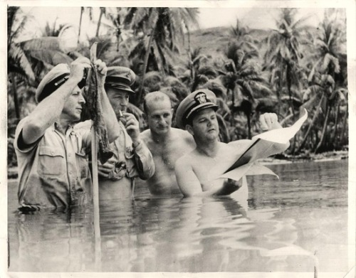 "1942- U.S. officer and his advisers, up to their waists in water, are shown planning runway ramps for seaplanes while establishing a new base ""somewhere"" in the South Pacific."