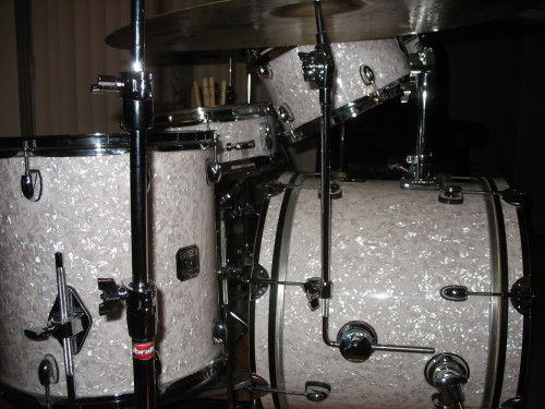"Here is a shot of my Catalina kit with a Gibraltar shell mounted cymbal holder. It usually sells for about $40. I installed this recently as it's something I've been wanting to do for a while. All you need is a drill with an 8mm (or 5/16"") bit and you're ready to go. The bracket comes with a rubber gasket that you can and should use as a template to mark the holes for drilling. I just taped it to the shell and drilled through the holes in the gasket. I like the bracket down at about the 3 o'clock position (from the drummer's perspective) but wherever you put it make sure it doesn't interfere with other things like lugs, spurs, etc. It's also a good idea to start with smaller holes and work your way up to the proper size and drill slowly to avoid splintering on the other side. The holder itself is simple but works well. It does wobble a little when a cymbal is mounted on it but it doesn't slip. If you think this may bother you, you may want to stick with a stand. See my post on Gibraltar's flat base stands below if you're into the vintage look. Those are great and can hug your bass drum really closely."