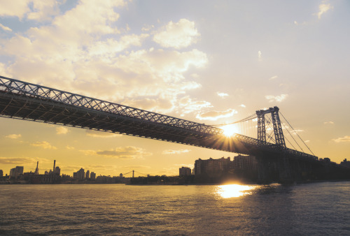"Williamsburg Bridge and the skylines of Manhattan and Brooklyn at sunset.—-  Moments are vessels that contain: sparks, magic, effervescent happiness, lingering sadness, red-tinged anger, bittersweet joy all waiting to explode if and when that point in time is visited again.  There are moments that exist somewhere between the excited beat of the heart and a welled-up tear in the eye. They are the chills that run up the back of the neck and the small smile that can't be contained when their memory is nudged by a sound, sight, scent, touch.  It's the way the light was shining through the bridge as the boat pulled away under a sky blue with hope as the sun set and the lump in the throat subsided momentarily. It's the way the water looked as it rocked the boat gently like a lullaby as it drifted away from the sunlight that poured its light onto the surface of the water.   And it's the way everything seemed pointless in comparison to the way the clouds gathered over the city: hopeful tufts of smoke emanating from the sun's extinguishing fire…  —-This is a view of the Williamsburg Bridge and the Lower East Side as seen from a boat on the East River during sunset with the Sony A77. In the distance sits the skyline of Brooklyn in Dumbo and the Manhattan Bridge.   —-View this photo with a comment thread on my Google Plus page—-View ""Williamsburg Bridge and New York City Skyline at Sunset"" in my photography portfolio here, email me, or ask for help."