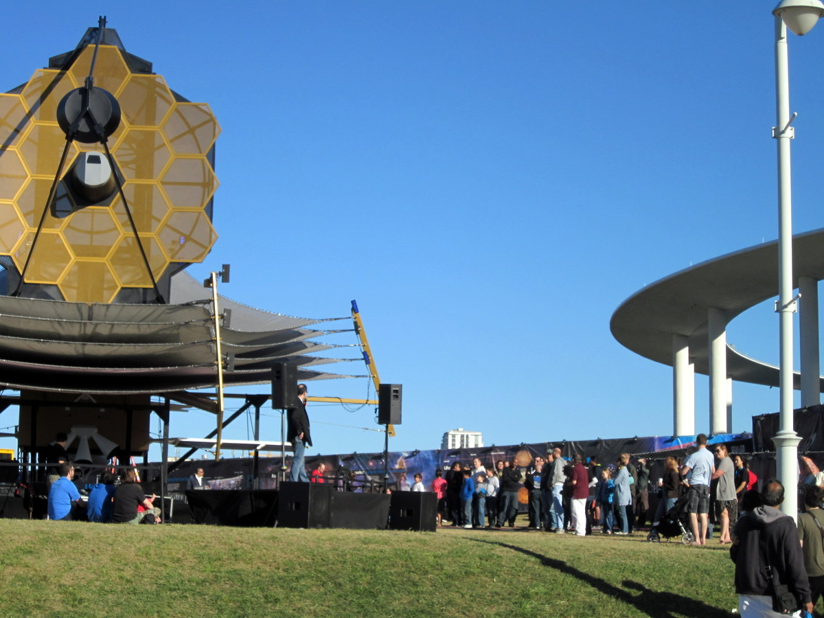 Man giving presentation outside the replica of the Webb telescope to a gathering public