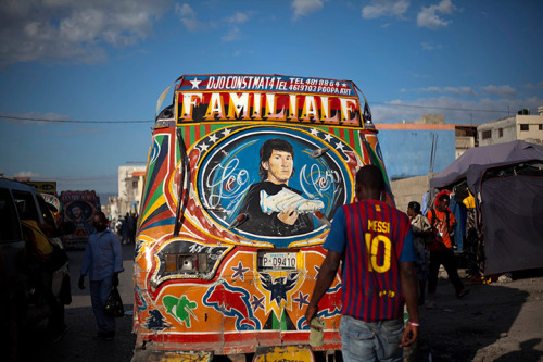 Port-au-Prince, Haiti: a man wearing a Barcelona FC Lionel Messi top walks behind a bus with an image of Messi. From 24 Hours in Pictures on The Guardian.