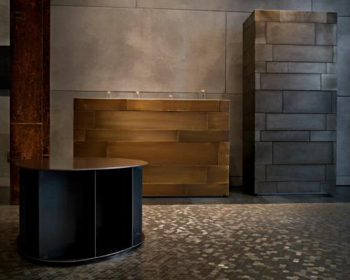 DeCastelli showroom Milan. Shown are the Celato chests clad in plates of acid etched brass and iron and a low Existence shelf by Michele DeLucci. All sitting pretty on DeCastelli's hex billet steel mosaic flooring….amazing!