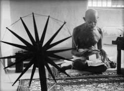 Mohandas Gandhi reading next to a spinning wheel at home, 1946, photo by Margaret Bourke-White
