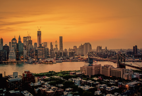 "New York City Skyline and the roof tops of Brooklyn Heights at sunset overlooking the Brooklyn Bridge.Summer evenings in New York City weave their own spell when summer night skies slide onto the city through the sticky-sweet haze.    The skyscrapers cling to the sunlight wrapped up in the glow and hazy anticipation of just one more kiss of light. —-This was taken at the peak of last summer from a roof top in Brooklyn overlooking the skyline of Brooklyn Heights, the Brooklyn Bridge and a very hazy lower Manhattan skyline. I was shooting with a camera I wasn't at all used to shooting with and the temperature was hovering near 80 degrees at night with nearly 100% humidity. The air was thick as molasses and the heat was unrelenting but it was an absolutely gorgeous summer sunset.   It's usually this point of the winter when I start pining for summer evenings like this forgetting that on summer evenings like this, I am usually pining for winter :).—-View this photo with a comment thread on my Google Plus page—-Buy ""New York City Skyline Sunset and the Brooklyn Bridge on a Summer Evening"" Posters and Prints here, email me, or ask for help."