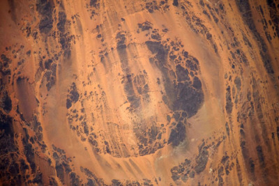 Aorounga crater is one of the best preserved impact craters on Earth, thanks in part to its location in the Sahara Desert in Chad. The 10 mile-wide crater is probably around 350 million years old. The stripes are alternating rock ridges and sand layers, known as yardangs, caused by persistent unidirectional wind. The image above was taken by astronauts in the International Space Station in July.