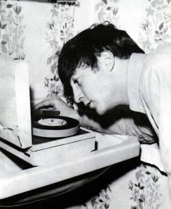 """john-lennons-sideburns:  John Lennon listening to a 45""""  *7"""" 45-rpm single. Not 45""""."""