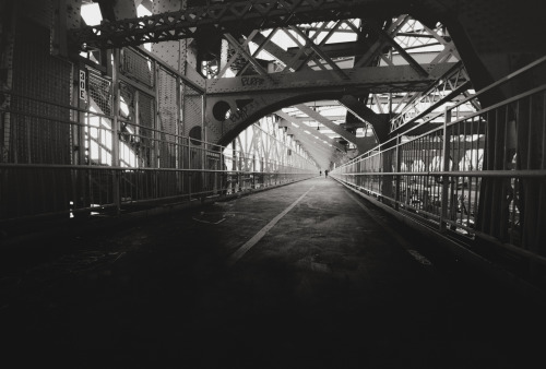 "Williamsburg Bridge pedestrian walkway. New York City. I have been on a strange sort of journey lately when it comes to photography. And I have noticed a shift in my vision or rather a slight deepening of meaning that I am seeking when it comes to the imagery I have been consuming and capturing. I have been watching a tremendous amount of documentaries about photography and photographers trying to understand where my own peculiar sort of artistic unrest is originating from. I suspect the angst has to do with a visual tiredness and unease at the overwhelming amount of imagery that seems to be in circulation at any given moment online. I am pondering writing a series of essays on the rise of mass consumption and sharing and how it correlates to various trends in offline photography but the ideas are all still percolating.   A series that really, really touched me though is called Contacts. I devoured all of Contacts: Volume 2 - The Revival of  Contemporary Photography  and Contacts: Volume 3: Conceptual Photography over the course of two nights.  It's a collection of tiny vignettes that explore different photographer's contact sheets and/or body of work while they explain or talk about their work. I think I have watched the vignette of Sarah Moon's work set to her stream-of-consciousness description of her own inward photographic journey over a dozen times at this point (it even ended up on my ""Scenes that have stuck to my ribs and clung to my heart"" playlist on Youtube: the ultimate testament to it becoming a part of my consciousness permanently ;) ).   When I first watched it and listened, I could barely stop the tears from flowing because it was absolutely perfect (and even that would be an understatement):   Contacts: Volume 2 - Sarah Moon  —-  I had an entirely different set of thoughts I wanted to include with this image of the Williamsburg Bridge (taken with the trusty Sony A99) but I seem to have veered in a different direction perhaps because all of this has been on my mind for weeks. And that's fine, now that I think of it, because in some ways, there couldn't be a more fitting recent image to accompany this post.  ""Time goes by. Light falls. I lose confidence. I don't want to be a photographer anymore…  Then, all of a sudden, but not always, something changes, I can't say why, maybe I'm just in the right place at the right time, or maybe I believe in it.    However, for a split second, I see a sparkle of beauty passing by, everything goes so quickly now within that stillness, and I'm carried away, and at last I like what I see, and I can't stop finding it, then losing it, and all day long I keep on, because it once existed."" - Sarah Moon   —-View this photo with a comment thread on my Google Plus page—-View ""Willamsburg Bridge - New York City"" in my photography portfolio here, email me, or ask for help."