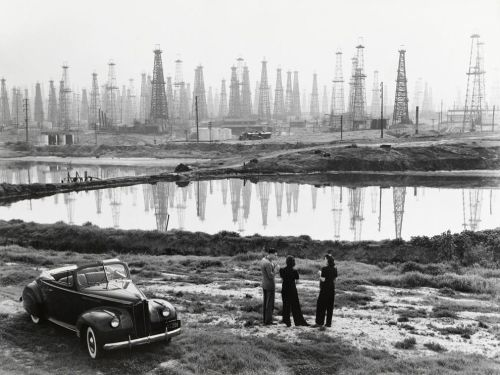 bartleby-company:  A forest of oil derricks makes a ghostly backdrop for a conversation in Signal Hill, California, 1941, by B. Anthony Stewart