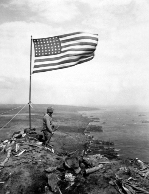 A Marine standing on top of Mt. Suribachi, Feb 1945