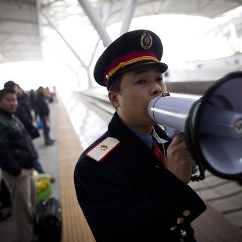 A train conductor announces the arrival of a train at the Guangzhou South railway station in Guangzhou, China, January 11, 2013. (John Lehmann/The Globe and Mail) #china #mao #photojournalism
