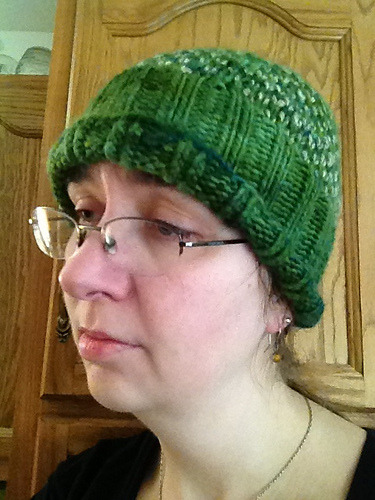 "Local Handspun Hat My favorite yarn store randomly got their hands on some yarn from Breezy Manor Farm in Mooresville.  Handspun from the coats of animals raised on the farm and hand-painted, it's the sort of stuff I don't often get an opportunity to pick up.  I had a gift card burning a hole in my pocket, it was delicious yarn, and there was even a lovely green colorway that seemed to call out to me.  (""Kniiiiiiit meeeeee!"")  So I got it without having any idea what I was going to do with it, even though I've promised myself not to do that anymore. When I found the Chance of Flurries pattern, I realized that it would be a perfect way to also put to use the handspun from Spring Mill State Park that I'd picked up a while ago.  Being only 55 yards, it wasn't enough to make anything out of on its own, but it could perfectly well be an accent.  Plus, it would be an opportunity to dip my toe into the world of colorwork. Unfortunately, it's one of those times when swatching was no help.  I swatched, went down a needle size, swatched again, and set off happily thinking I'd gotten the perfect gauge.  The I got most of the way through the hat and actually thought to measure my gauge again, and…  I should have stuck with the larger needles. So the hat is a bit on the small side.  Still, I'm very happy with the way it turned out.  The yarn was wonderful, the finished product looks really nice…  I just wish it fit better."