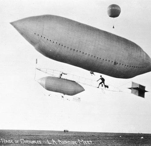 "xplanes:  ""(1910) - Photograph of dirigible race in the Dominguez Air Meet, Dominguez Field, Los Angeles, 1910. Two football-shaped zeppelins race across the skies, flying at low altitude. Each of them has single pilots. The pilots stand on a skeletal structure consisting of metal bars that is attached to the balloon with wires. Spectators (or judges) stand below on the plain field watching the zeppelins race. Further in the sky is a hot-air balloon with the phrase ""all in the Examiner."""" (via)"