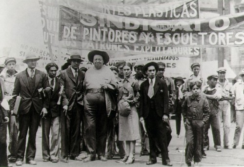 "garconniere:  Diego Rivera and Frida Kahlo in the May Day march, 1929, photographed by Tina Modotti ""Modotti joined the Communist Party in late 1927, often supplying it free photographs. Some of her photographs appeared in the Mexican Communist newspaper, El Machéte. To support herself, Modotti made record photographs for the Mexican muralists and of Mexican crafts for publishers. During this same period, some of her art photographs were published in the Paris Left Bank avant garde art magazine, transition. On the May Day Communist holiday in 1929, Modotti photographed a march protesting the persecution of members of the Communist Party. She covered the event from its calm beginning to its confrontational end. Most of the photographs that make up her narrative are small images made from a rooftop."" by Beverly W. Brannan, from Women Photojournalists"