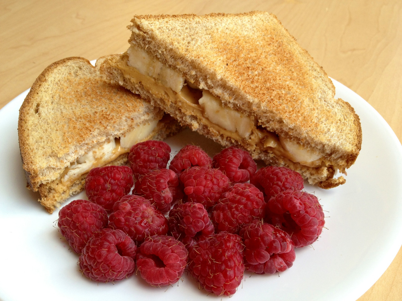 veggieomnom:  Whole wheat toast with white chocolate wonderful peanut butter, banana slices, raspberries, and a glass of almond milk.