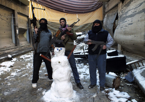 reuters:  Members of the Free Syrian Army pose with their weapons and a snowman at the Jouret al Shayah area in Homs January 10, 2013. REUTERS/Yazan Homsy PHOTOS: Snowfall in the Middle East