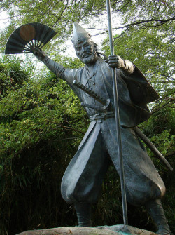 Statue of Kato Kiyomasa holding a war fan made of iron, bamboo and lacquer depicting the sun.