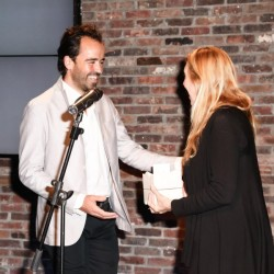 Photo: Matteo Prandoni/BFAnyc.com. Iwan Baan accepting his Architizer A+ Relevance Award from Lisa Phillips, director of the New Museum. 2013. [via architizer.com].