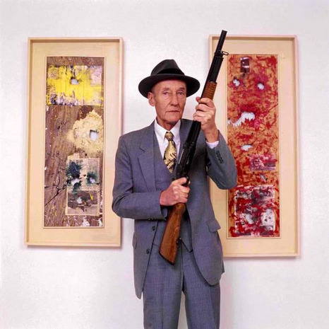 William Burroughs in front of two of his paintings.