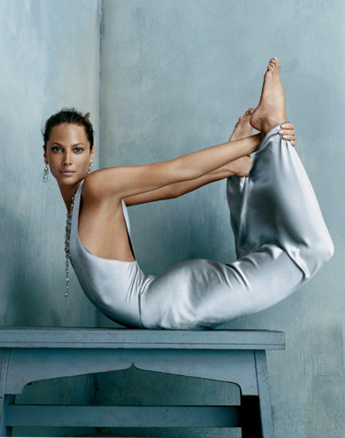 Pose of the Day: Dhanurasana or Bow Pose Done elegantly here by model & yogi Christy Turlington 1.Lie on your belly with your hands alongside your torso, palms up. (You can lie on a folded blanket to pad the front of your torso and legs.) Exhale and bend your knees, bringing your heels as close as you can to your buttocks. Reach back with your hands and take hold of your ankles (but not the tops of the feet). Make sure your knees aren't wider than the width of your hips, and keep your knees hip width for the duration of the pose. 2Inhale and strongly lift your heels away from your buttocks and, at the same time, lift your thighs away from the floor. This will have the effect of pulling your upper torso and head off the floor. Burrow the tailbone down toward the floor, and keep your back muscles soft. As you continue lifting the heels and thighs higher, press your shoulder blades firmly against your back to open your heart. Draw the tops of the shoulders away from your ears. Gaze forward. 3With the belly pressed against the floor, breathing will be difficult. Breathe more into the back of your torso, and be sure not to stop breathing. 4Stay in this pose anywhere from 20 to 30 seconds. Release as you exhale, and lie quietly for a few breaths. You can repeat the pose once or twice more.
