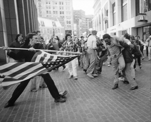callingoutbigotry:      historicporn:  Man uses American flag to assault civil rights activist.1976.    this is like something a political cartoonist would draw as a heavy-handed metaphor for race relations in the US except it actually happened