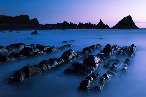 Hartland Quay on Flickr.Dusk across the bay at Hartland Quay. Taken last May. After lots of scrambling over the slanted rocks (seen in the background here) as soon as the sun went down I moved for a wider shot across the beach as the tide came in.