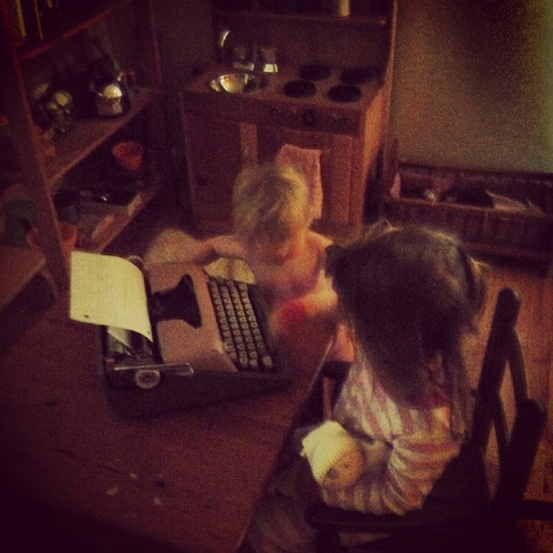 Lil teaching Eva how to use the typewriter