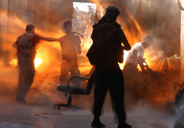 """In one of the most iconic images yet to come out of Syria's civil war, a band of rebels in an outpost in Aleppo are captured in this video frame at the exact moment a tank shell slammed into them. The only survivor, in addition to the photographer, was the one in dark silhouette, closest to the camera. Global Post's Tracey Shelton said she was filming a feature on life on the frontlines of Aleppo, camping out with the men of Noor Den al-Zenke batallion, in a two-block stretch of backstreets that had formed the final line between government troops and opposition forces. The men had been warned a tank was approaching, and were grabbing their weapons when a shell hit."" (GlobalPost/Tracey Shelton)"