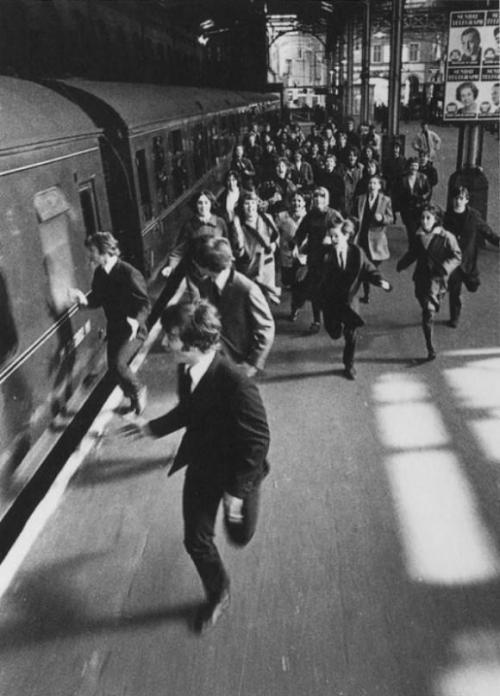 The Beatles running from fans on platform (Photo by Robert Freeman)
