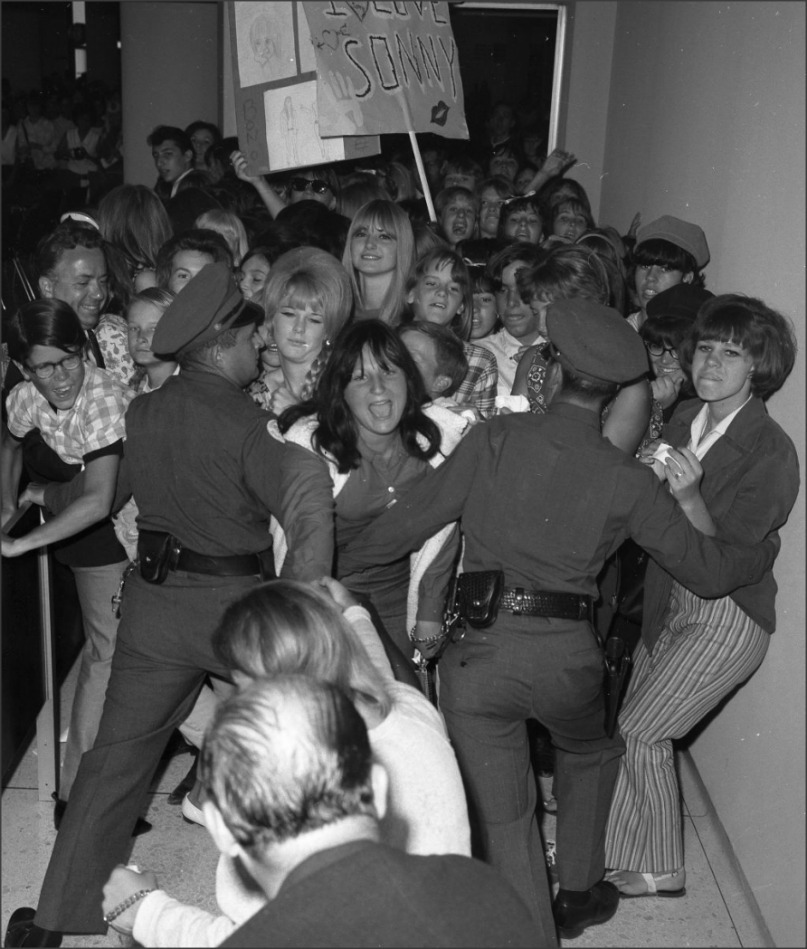 Teens, 1965 Police try to hold back part of 1,000 teenagers who broke through cordon at Los Angeles  International Airport to rush plane on which folk singers Sonny and Cher were leaving for a London engagement.