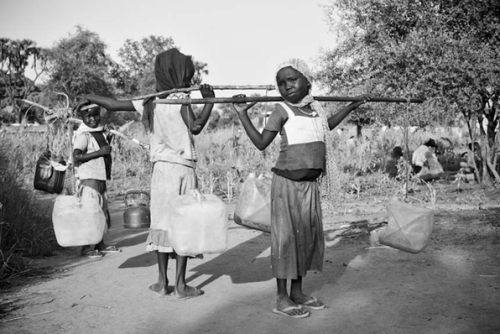 Girls carrying water at the Doro refugee camp in Maban, Upper Nile state in South Sudan. Female refugees and humanitarian agencies say that the risk of physical and sexual assault while collecting water or firewood is one of the gravest safety ad security concerns faced by female refugees. According to the UNHCR, the United Nations refugee agency, girls (under 18) are 32 percent of the entire Blue Nile refugee population registered in the four camps in Upper Nile state, South Sudan. © 2012 Samer Muscati/Human Rights Watch