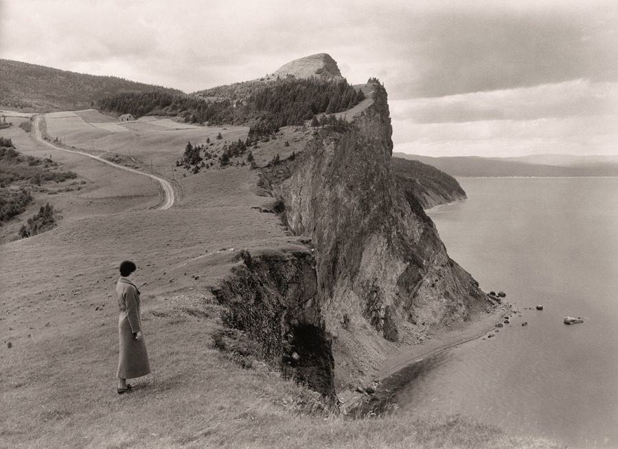 A woman stands before limestone cliffs in the Gaspe Peninsula, Quebec, September 1934.Photograph by B. Anthony Stewart, National Geographic