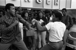 theyebies:  Muhammad Ali draws a crowd as he playfully spars with an fan in the parking lot of a grocery store in Miami Beach in 1971.