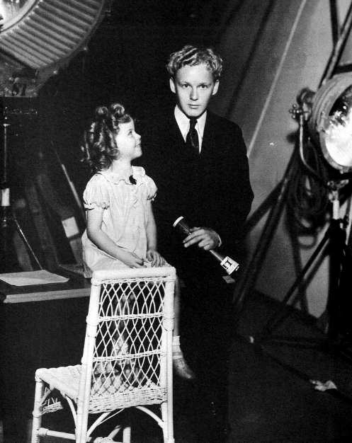 Shirley Temple on a sound stage, 1930s. Does anyone know who she is with here? I have quite a few images of her with mystery people and I can't seem to work out their names, even with a google image search of their face! I might be really stupid and this guy might be really famous, but I really have no clue. Please message me if you know!
