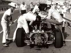 "The Shelby-American crew working on the Lang Cooper ""King Cobra"" driven by Dave MacDonald at the newly constructed Phoenix International Raceway, 1964. The car's engine had blown after qualifying the previous day, and a replacement engine was brought in from LA and quickly wrenched the morning of the race. MacDonald got in only three laps on the new engine before being fitted on the grid, 30 seconds before the flag fell. –Image by Dave Friedman"