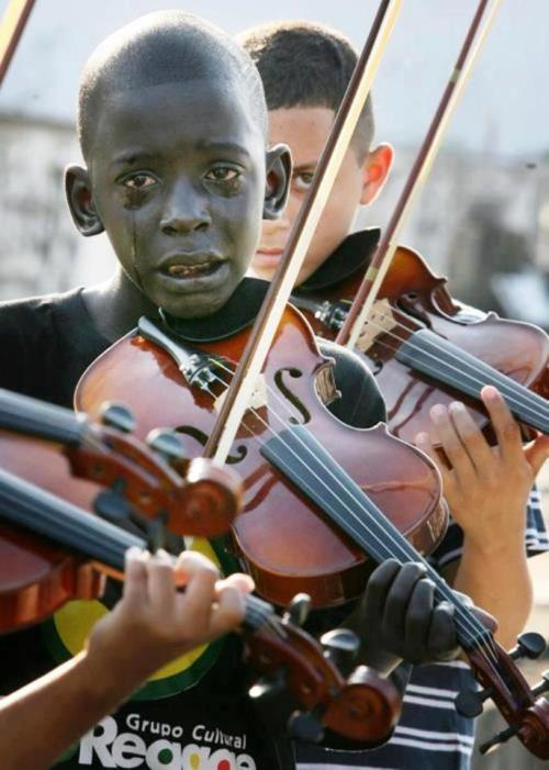 "liddohsav:  revolutionaryriots:  ""The music is played with the heart and is felt with the soul"" This is a picture of a brazilian kid who was part of the ""cultural group of reggae"", playing his instrument in the funeral of his mentor who saved him from an environment of poverty and crime. He was rescued from the street.  can't not reblog."