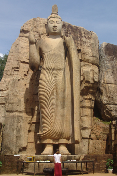 kelledia:  Fifth-century Aukana Buddha, Sri Lanka. The Buddha is 12m high (though it appears much, much taller) and is completely carved from the rock behind it, as is the case at Gal Vihara. But this Buddha is taller than those at Gal Vihara, and the work that went into it must have been immense. It is in extraordinary condition (the last chiseling could have been done the morning we saw it), which is truly amazing considering it is more than 1500 years old and has never been shielded from the elements by a roof or covering of any sort. This Buddha has risen in importance in the last seven or eight years after the unforgivable destruction of the twin Buddha statues (which were similar in design but much larger) in Bamiyan, Afghanistan by the Taliban.
