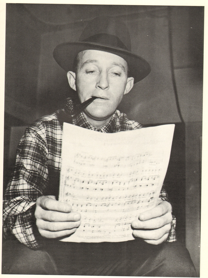 Bing reads. nprfreshair:  Kevin Whitehead on Bing Crosby's influence on popular music:  Bing Crosby's influence on modern singing is so huge, we barely notice it anymore. It spread out through deadpan crooners like Perry Como, folksy colloquialists like Johnny Mercer, and warm sexy baritones like Billy Eckstine. Later singers who effectively undersell a song are indebted too, like Nick Drake and Leonard Cohen.  Image of Bing Crosby reading the sheet music is from a CBS radio recording session in the fall of 1954, at the CBS studio in Hollywood courtesy of HLC Properties Ltd.