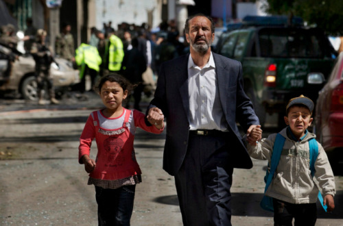 simply-war:  A man directed his children away from the site of a bombing in Kabul. May 16, 2013. Anja Niedringhaus.
