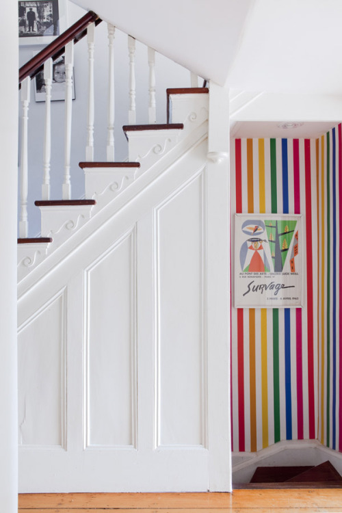 white staircase, colourful stripes downstairs! (via Orlando and Nicola Reindorf and Family | The Design Files)