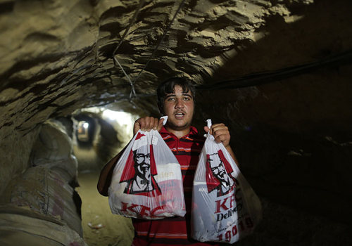 "slavin:  ""DELIVERY workers tramp through tunnels under Gaza — carrying bags and buckets of Kentucky Fried Chicken. The famous fast food has gone underground as Palestinians order the takeaways from Egypt. Boxes and bags emblazoned with Colonel Sanders famous red and white logo move swiftly through the smuggling tunnels that run beneath the border. The fried food has to make its subterranean journey across as there is no KFC restaurant in the Palestinian region. Israeli restrictions on Gaza crossings make it difficult to open an international fast food branch in the area."""