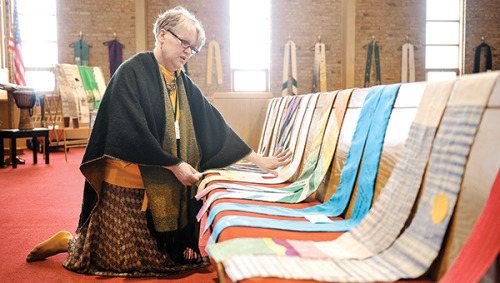 "'Shower of Stoles' exhibit supports LGBT [people] of faith  Seven members of First Congregational worked meticulously, well into the afternoon Friday as they hung 100 intricate, ministerial stoles. Their work was for more than just an art project, though. Shower of Stoles is a traveling exhibit of more than 1,000 religious garments donated by LGBT individuals who serve or have served in ministry but have been defrocked by the church for their sexual orientations. Martha Juillerat started the project when she stepped down from the Presbyterian Church in 1995 and came out, according to the project's website, www.welcomingresources.org. She asked for other LGBT [people] to send in their stoles to display and received 80 within the first day. The next spring, she had 200, so the first display was held in 1996 in Albuquerque, N.M. Over the years, clearly, the exhibit has grown. Now it is split up into pieces, and First Congregational is hosting the exhibit for the first time from May 3 to May 15. Member Vickie Spyhalski is one of the seven who helped hang the stoles, which took several hours. ""The purpose is really to show the role that LGBT people play in the church and their role in the ministry,"" Spyhalski said. First Congregational has 100 of the stoles on display. Many of them are coupled with the stories of the people who wore them and the struggles they faced by coming out. Those stories, Spyhalski said, are powerful. ""It's very moving when you get to see them,"" Spyhalski said. ""I actually hung a stole of a man who died of AIDS who was a minister. When you hang a stole and you realize he's no longer with us, really it is a very sacred thing."""