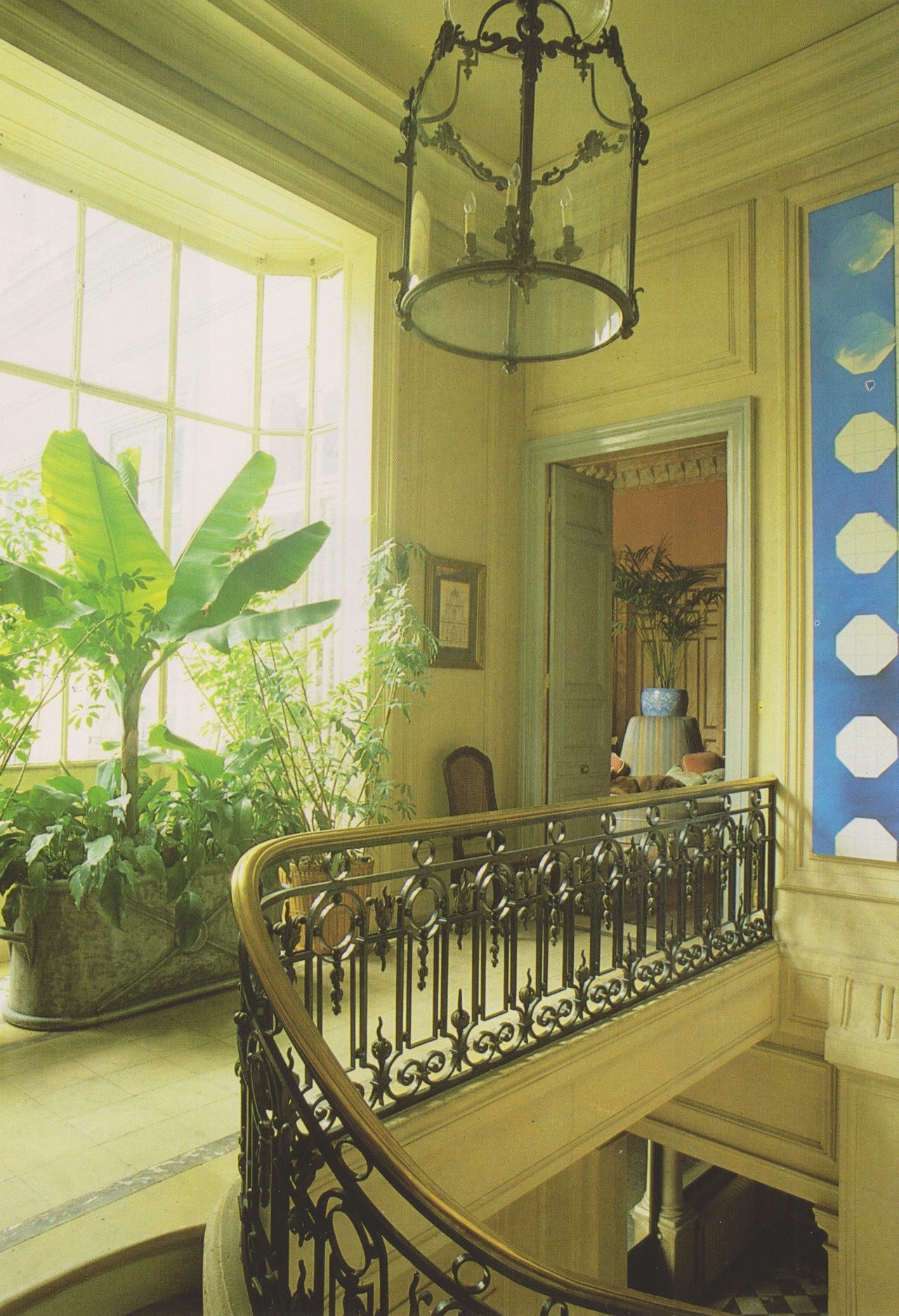 A 19th-century lantern hangs over the stairs; an antique bathtub from the Marche aux Puces, filled with plants, brightens the landing.The French Touch: Decoration and Design in the Most Beautiful Homes in France, 1988 #vintage#vintage interior#1980s#interior design#home decor#staircase#landing#lantern#brass#bathtub#plants#bay window#marble#French#apartment#city living#style#home#architecture#antique