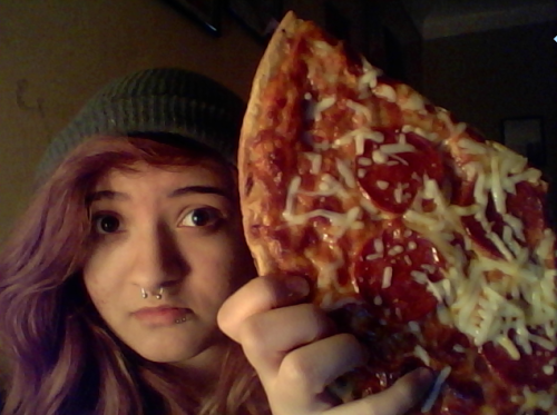 "My brother just gave me this rather large ""slice"" of pizza after taking a bite out of it."