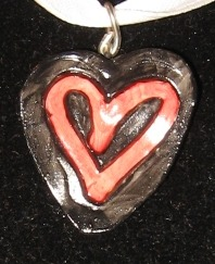 Red and black heart - this one's actually smaller than usual, about an inch tall. Polymer clay & paint, sealed.