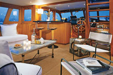 Nautical boat bar with captain's stools & ship's wheel on a yacht.