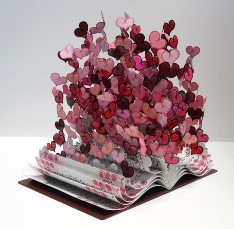 "Book Of Love by David Kracov  Inspired by David's love and passion for reading and poetry, the pages of ""Book Of Love"" transform from the prose of the likes of Browning, Frost, Shelley, and Byron, into a colorful burst of hearts. ""Book Of Love"" is a hand-made, one-of-a-kind, steel sculpture, and David writes different prose and poems in every sculpture, so each and every ""Book Of Love"" is truly unique. Romantic and tragic, short lived and everlasting, every love has a story."